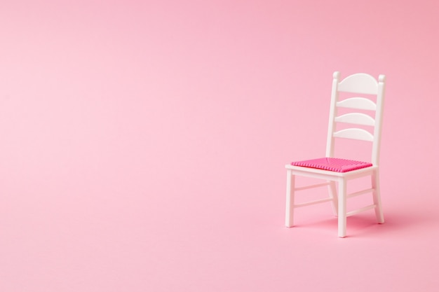 White chair with red seat on pink . furniture composition.