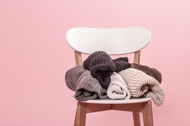 White chair with a stack of knitted sweaters on a pink wall