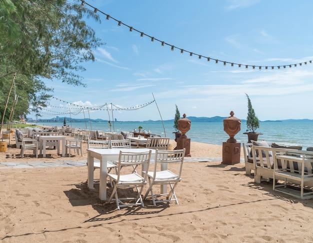 青い海と澄んだ空の眺めを持つビーチの白い椅子とテーブル