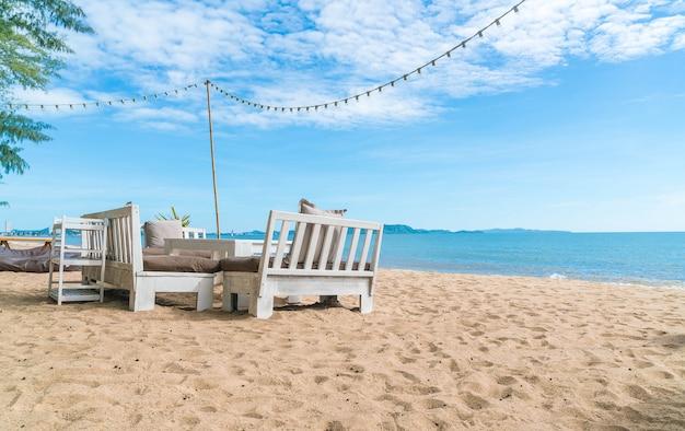 Белые стулья и стол на пляже