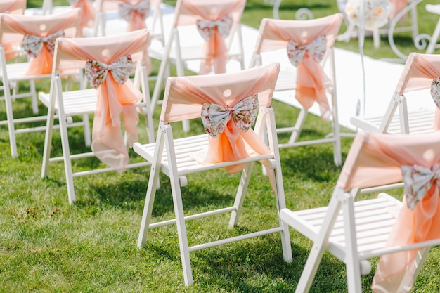 White chairs decorated with bows are on the nature