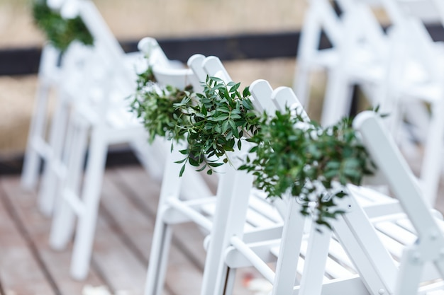 White chairs decorated with greenery and eucalyptus are in the zone of the wedding ceremony on the pier