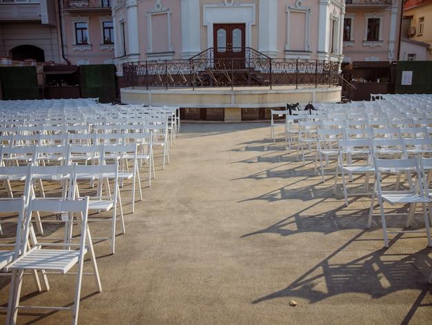 屋外コンサートホールの視聴者のための白い椅子