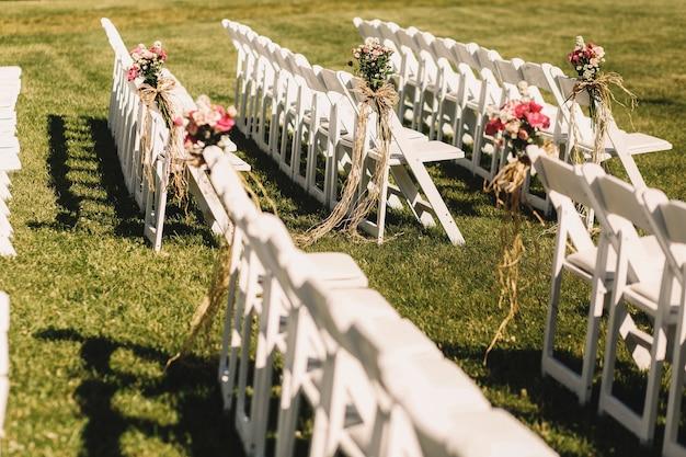 Белые стулья стоят в длинных рядах, ожидая начала свадьбы