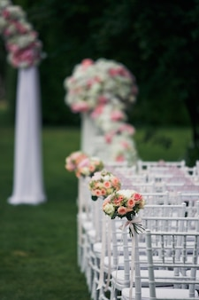 White chairs stand in the rows on green lawn