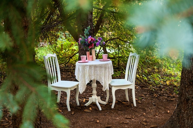 White chairs, a table with pink cups, a candle and a bouquet of flowers.festive photo area on the street with furniture, free space. holiday concept