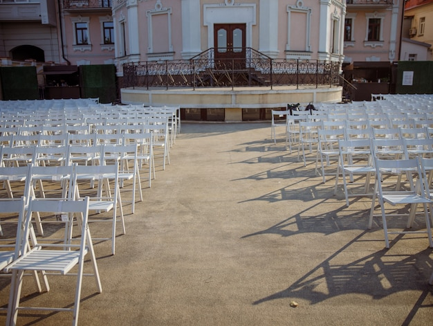 White chairs for viewers at outdoors concert hall