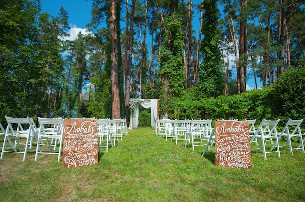 White chairs and wedding arch for the ceremony in the woods