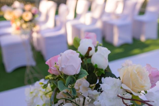 結婚式の出口登録のためのピンクの弓と白い椅子。