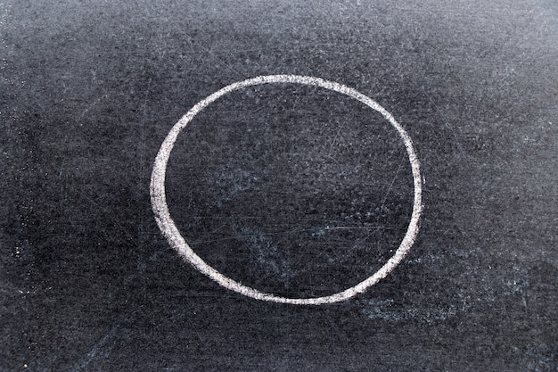 White chalk hand drawing in circle or round shape on black board background