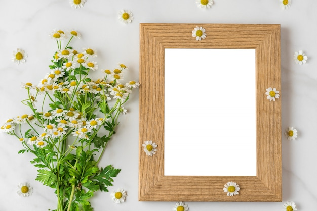 White chamomile flowers bouquet with blank photo frame on white. flat lay. top view
