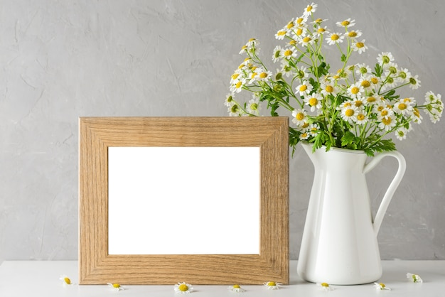 White chamomile flowers bouquet with blank photo frame on white. still life