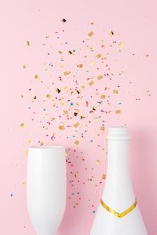 Белая бутылка шампанского и бокал шампанского с конфетти на розовой поверхности.