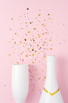 White champagne bottle and champagne glass with confetti on pink surface.
