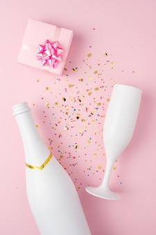 Белая бутылка шампанского, подарочная коробка и бокал шампанского с конфетти на розовой поверхности.