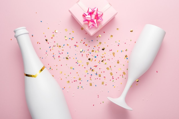 White champagne bottle, gift box and champagne glass with confetti on pink background.