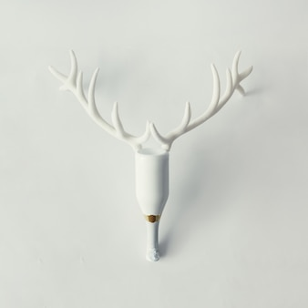 White champagne bottle with reindeer antlers on bright surface