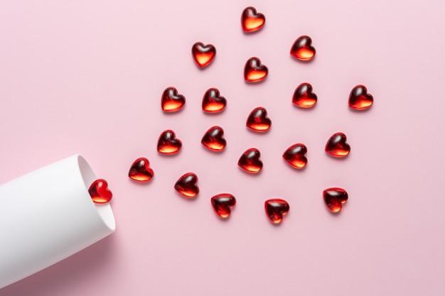 Белый бокал шампанского с сердечками красного стекла над розовой поверхностью.