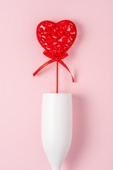 Белый бокал шампанского с красным сердцем над розовой поверхностью.