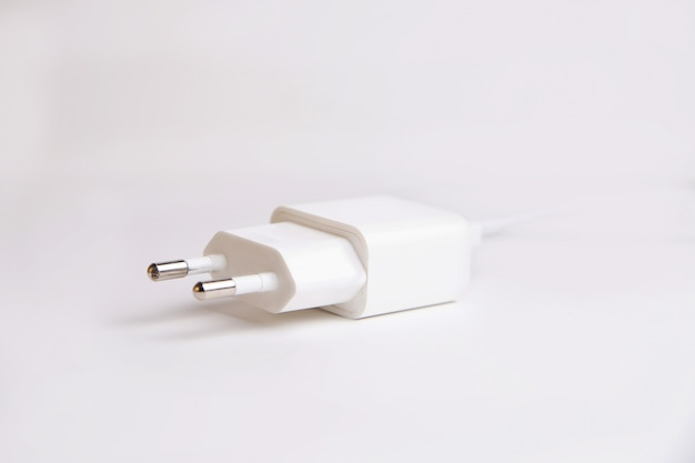 White charger adapter for smartphone on a white wall