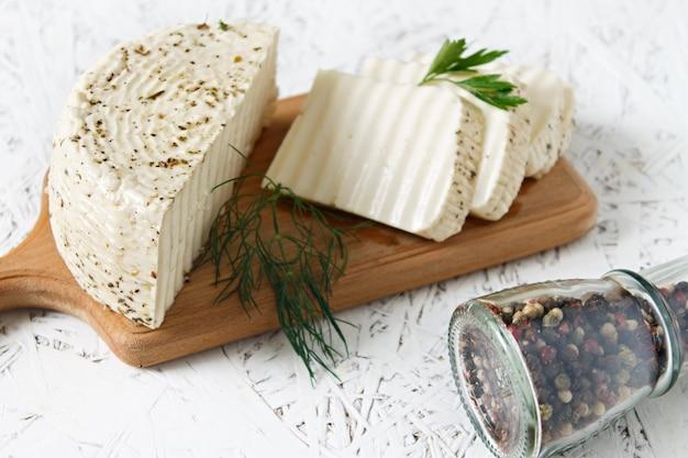 Белый сыр и специи на деревянной доске на белом фоне