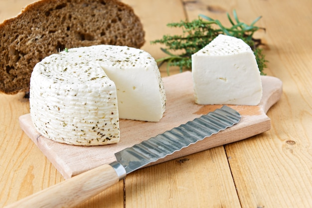 White cheese and bread on a wooden background and greens