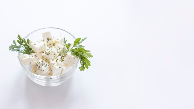 White cheese cubes with parsley in the glass bowl on white backdrop