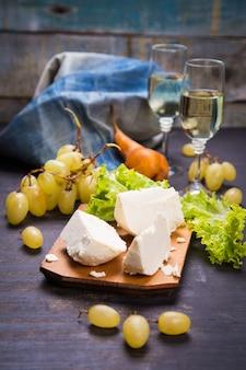 Белый сыр, виноград и листья салата с белым вином
