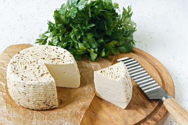 Белый сыр на деревянной доске на белом фоне с зеленью