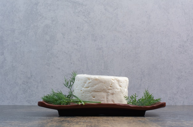 딜으로 갈색 접시에 흰색 치즈입니다.