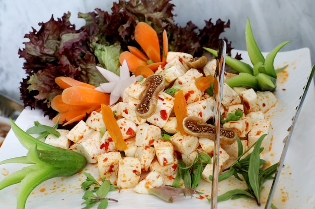 White cheese pieces with mixed vegetable  hot sauce on catering plate