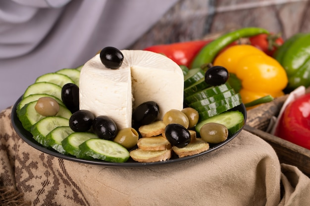 White cheese platter with cucumber and olives