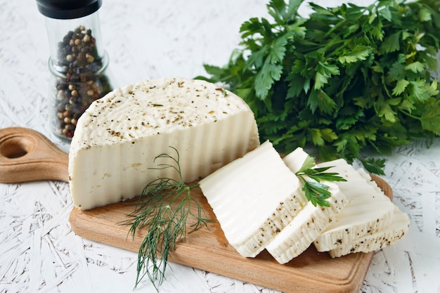 White cheese and spices on a wooden board on a white background