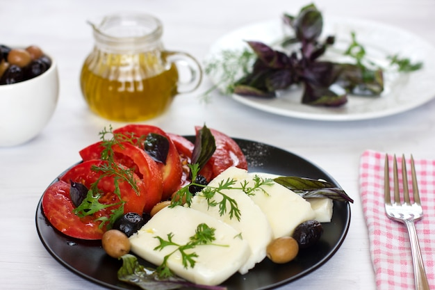 White cheese with tomatoes, green and black olives, basil, coriander and olive oil