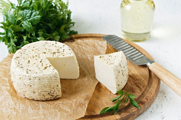 White cheese on a wooden board on a white background with greens