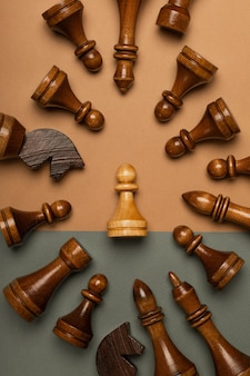 White chess pawn surrounded by black chess pieces on flat background
