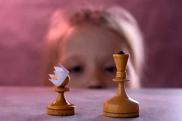 White chess pawn with a paper crown on its head against the white queen
