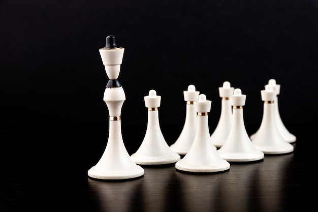 White chess pieces on a chessboard on a dark background. business concept.