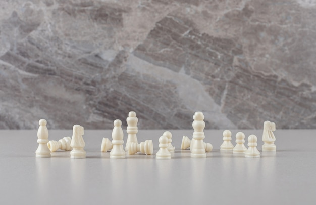 White chess pieces displayed on marble
