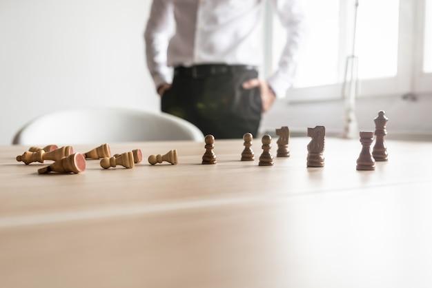 Белые шахматные фигуры лежат упавшими и черные фигуры стоят на офисном столе