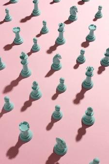 Белые шахматные фигуры на розовом фоне