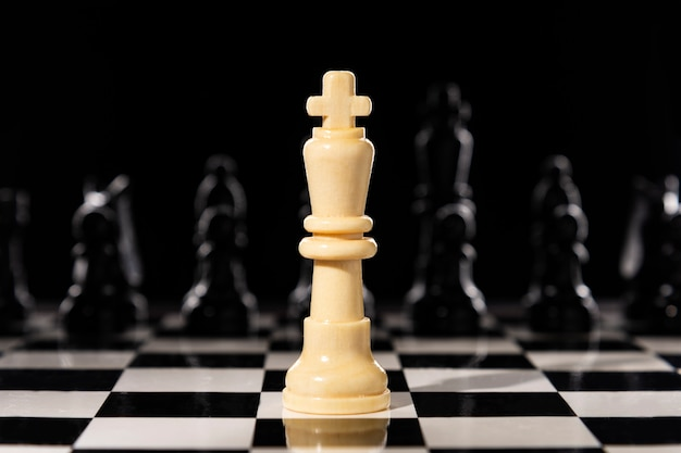 White chess queen on a chessboard against black chess pieces