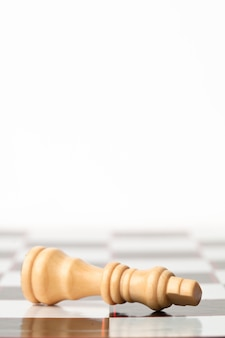 White chessman lying at the chessboard