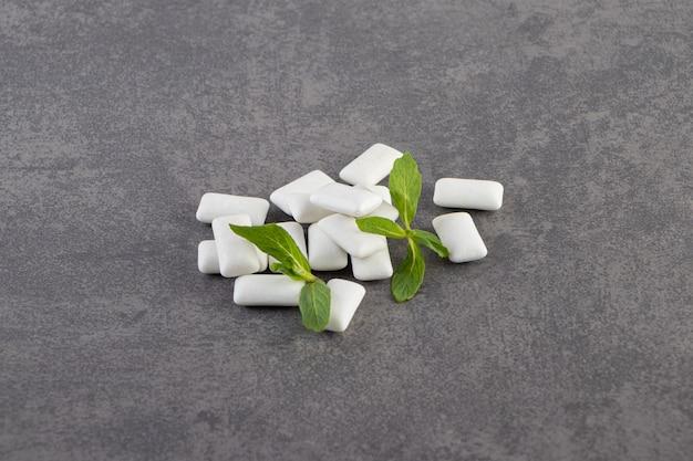 민트 잎이 달린 흰색 껌을 돌 테이블 위에 놓았습니다.