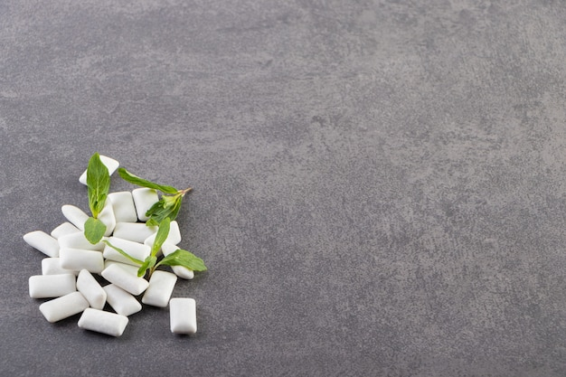White chewing gums with mint leaves placed on a stone table .