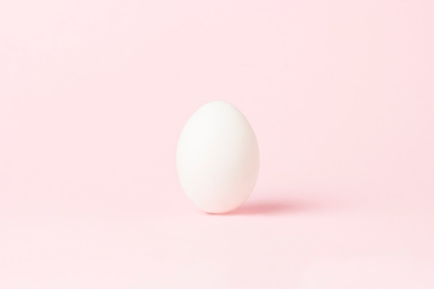White chicken egg on a pink surface. minimalism. side view.