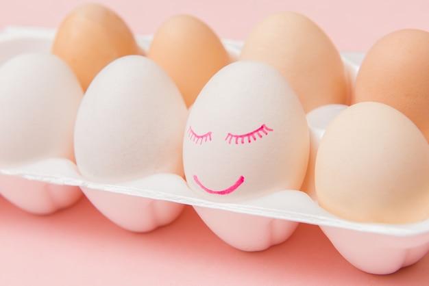 ピンクの卵ボックスに顔と笑顔が描かれた白い鶏の卵
