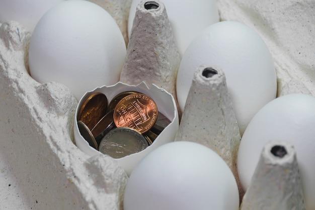 白い鶏の卵は段ボール箱に入っています。それらの1つが壊れていて、それはアメリカのセントでいっぱいです