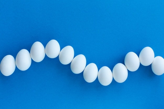 White chicken eggs on a blue background lined with wave