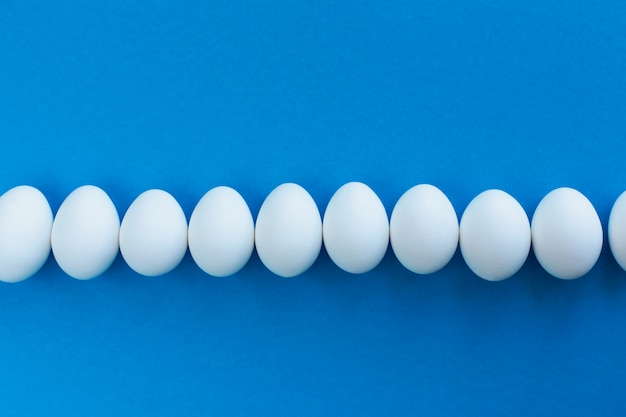 White chicken eggs on blue lined with a line